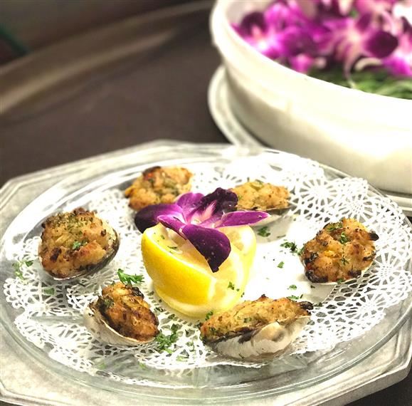 Panza's Clams Casino on a plate with a lemon and garnished with a flower