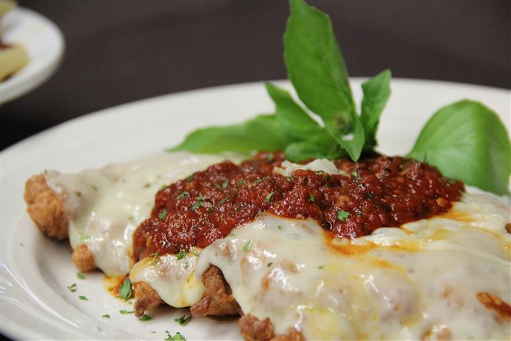 chicken parm with sauce, cheese and herbs