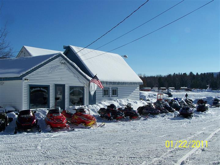 snowy marina with several snowmobiles in the parking lot