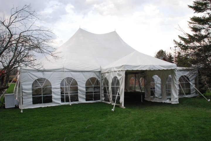 White tent with windows on area of green grass.