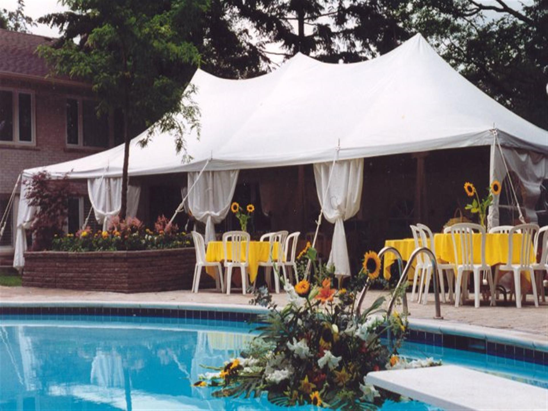 White tent, tables, and chairs poolside