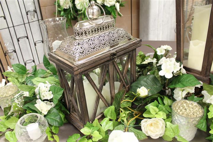 a glass cage with candles in it with white and green floral vines
