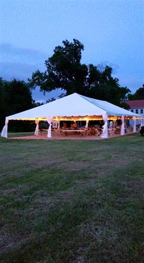 a white tent outdoors with lights