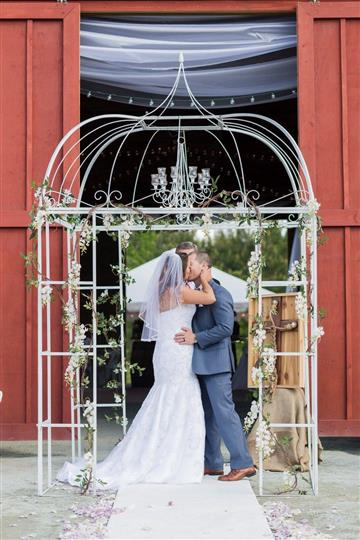 bride and groom kissing in front of a white cage