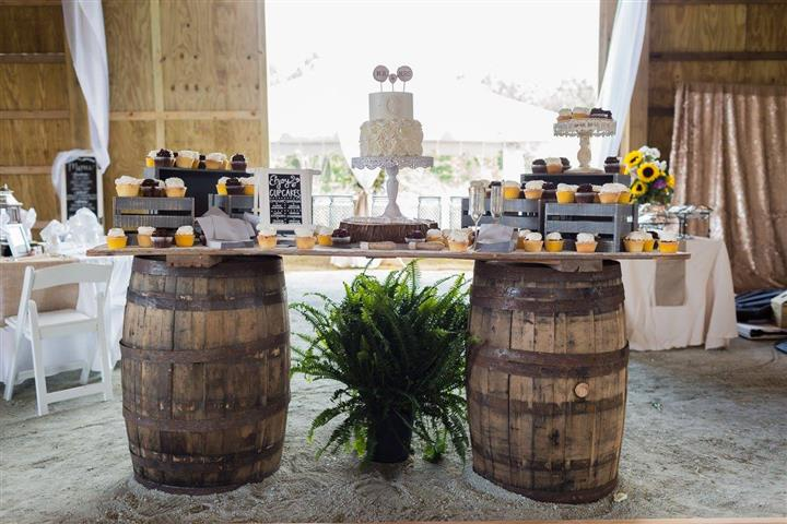 wooden barrels holding up a dessert table with a wedding cake