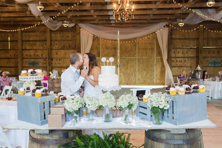 bride and groom kissing in front of the wedding cake in a barn