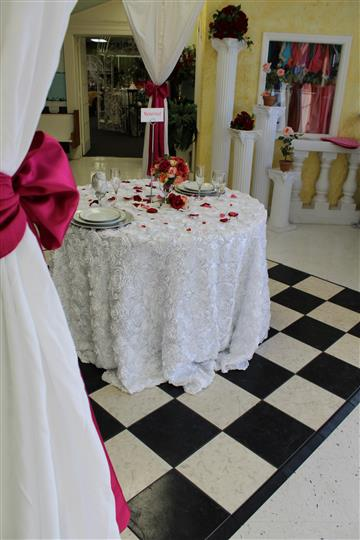table with white tablecloth and rose petals