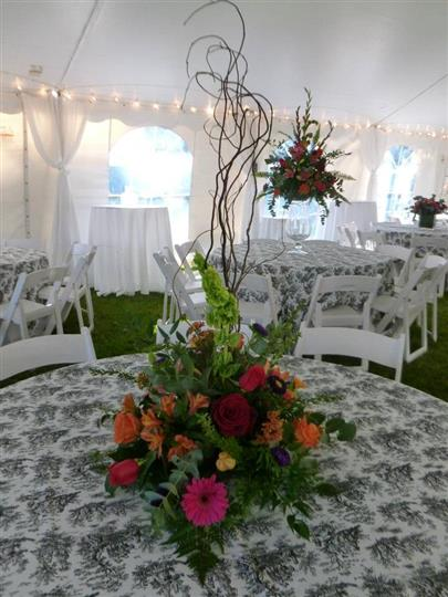 the view inside of a tent with lace tableclothes and floral centerpieces