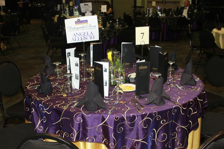 a dark purple table clothe with black napkins and name placecards