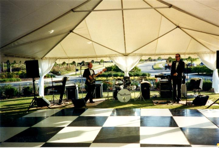 big white tent with a band under it with a checkered dance floor