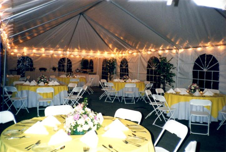 white tent with lots of chairs and tables with yellow tablecloths