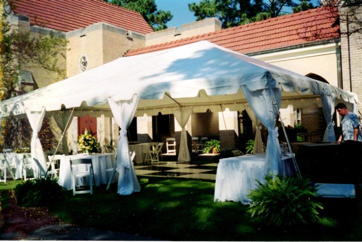a big white tent outside of a rustic house