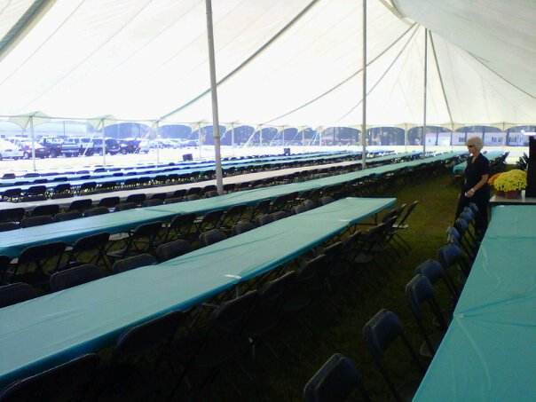 rows of tables and chairs under a huge white tent
