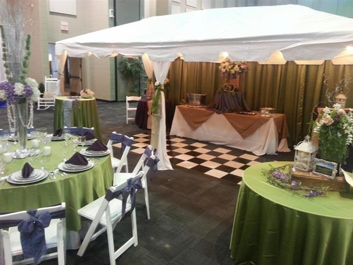 room of tables with green tablecloths and purple napkins with a white tent in the background