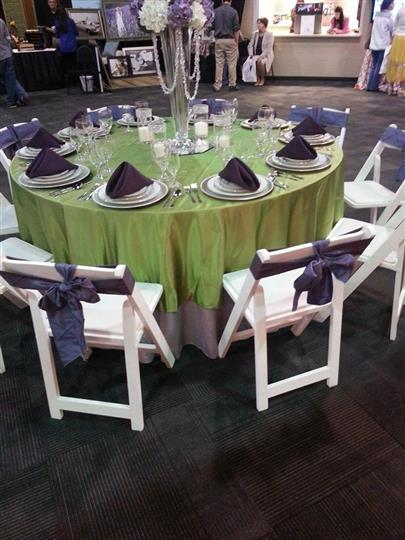 table with green tablecloth and dark purple napkins and 10 place settings and chairs