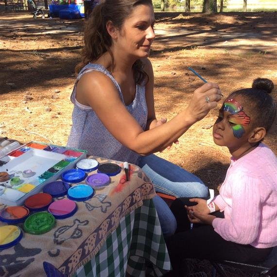 Young girl getting her face painted by adult female