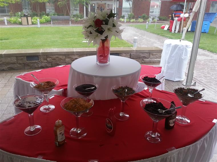 Outdoor catering table with dessert toppings in large martini glasses