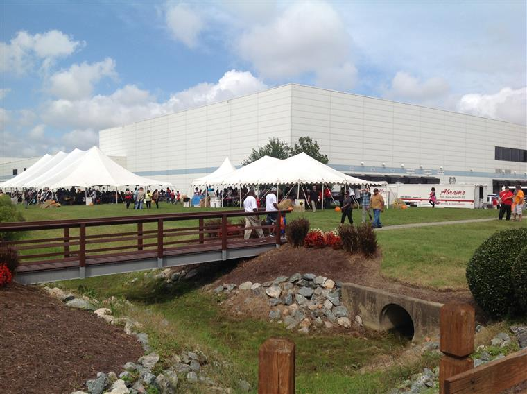 Outdoor scence of company gathering with building and tents
