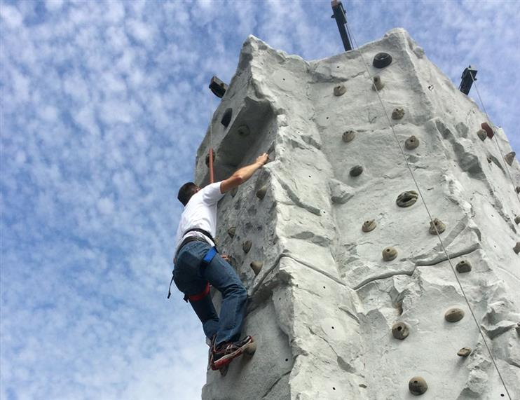 Harnessed man climbing synthetic rock wall