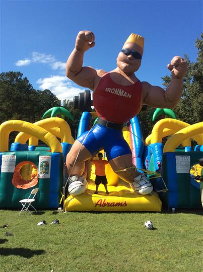 "an inflatable obstacle course with an inflatable man wearing a top that says ""Iron man"""