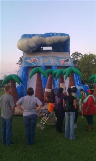 an inflatable bouncer with six inflatable palm trees, inflatable clouds and a line of parents with their kids