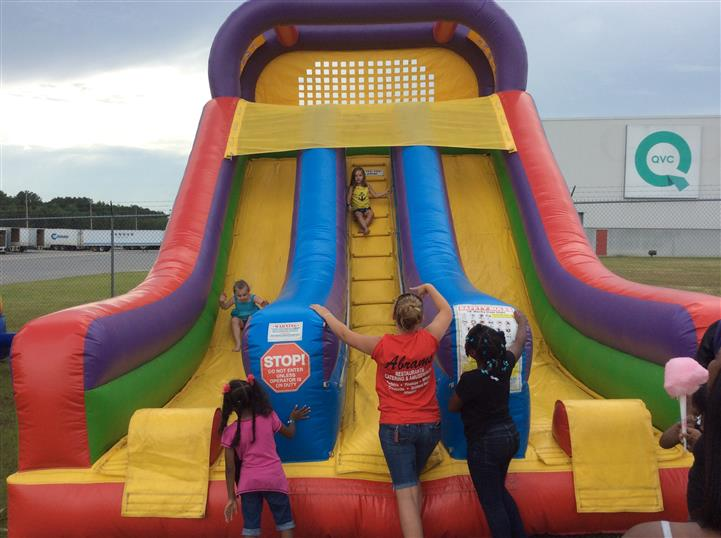 an inflatable bouncer with an attendant and four children playing