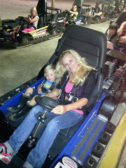 a mom and her son sitting in a go kart