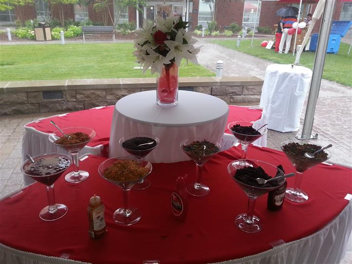 ice cream toppings on a red table with white flowers in a centerpiece