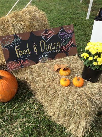"a hay bale with a chalkboard saying ""Food & Dining"" next to pumpkins"