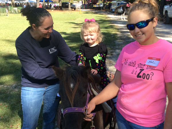 a little girl riding a pony with her mom next to her and an attendant watching