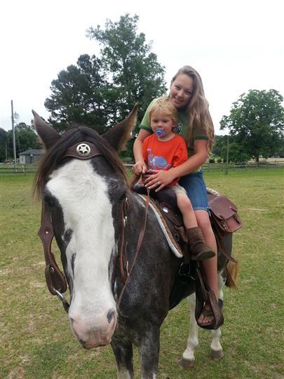 a mom and her son riding a pony