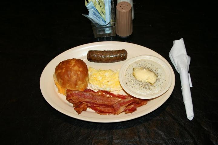 a plate of eggs, sausage, bacon, gravy and a biscuit