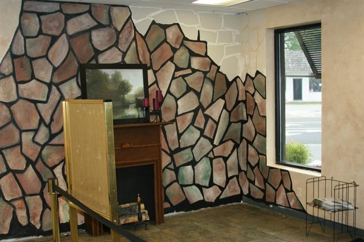 inside of restaurant showing fireplace and stone wall