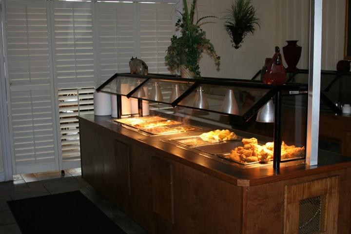 an area of buffet food under a heat lamp