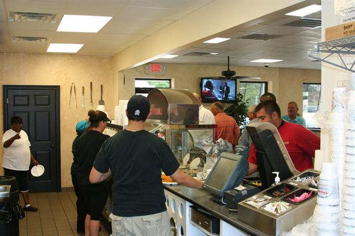 view of workers taking orders with many customers on line