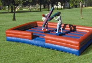 two kids wrestling on an inflatable area