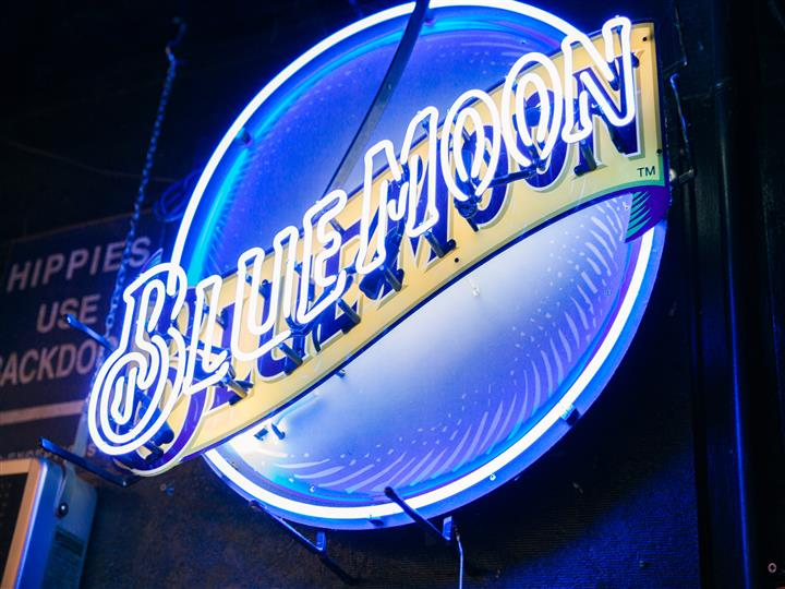 Neon sign for Blue Moon beer on interior wall