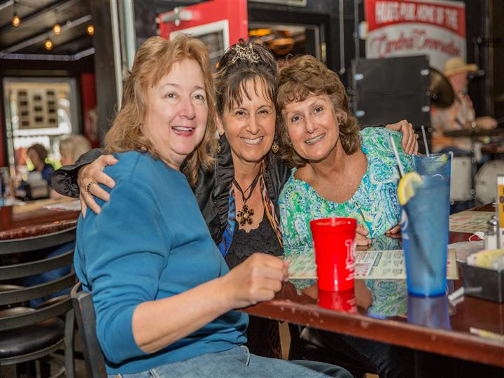 group of 3 women smiling for a picture at a table
