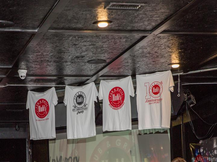Hubs & Pub grill t-shirts hanging up from the ceiling