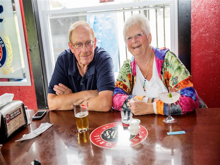 An couple of a man and a women taking a photo with two beverages on the table