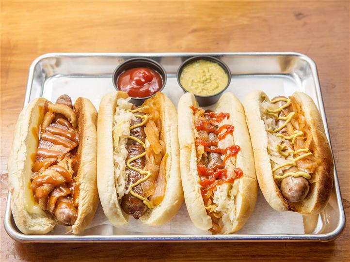 Bratwursts on a tray with assorted toppings and a side of ketchup and spicy mustard