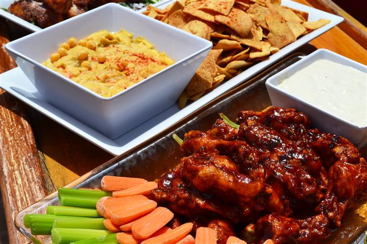 Plate of pita chips and hummus and a tray of buffalo wings with bleu cheese, carrots and celery