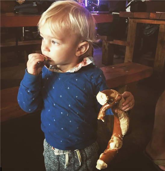 Child standing holding and eating a giant pretzel