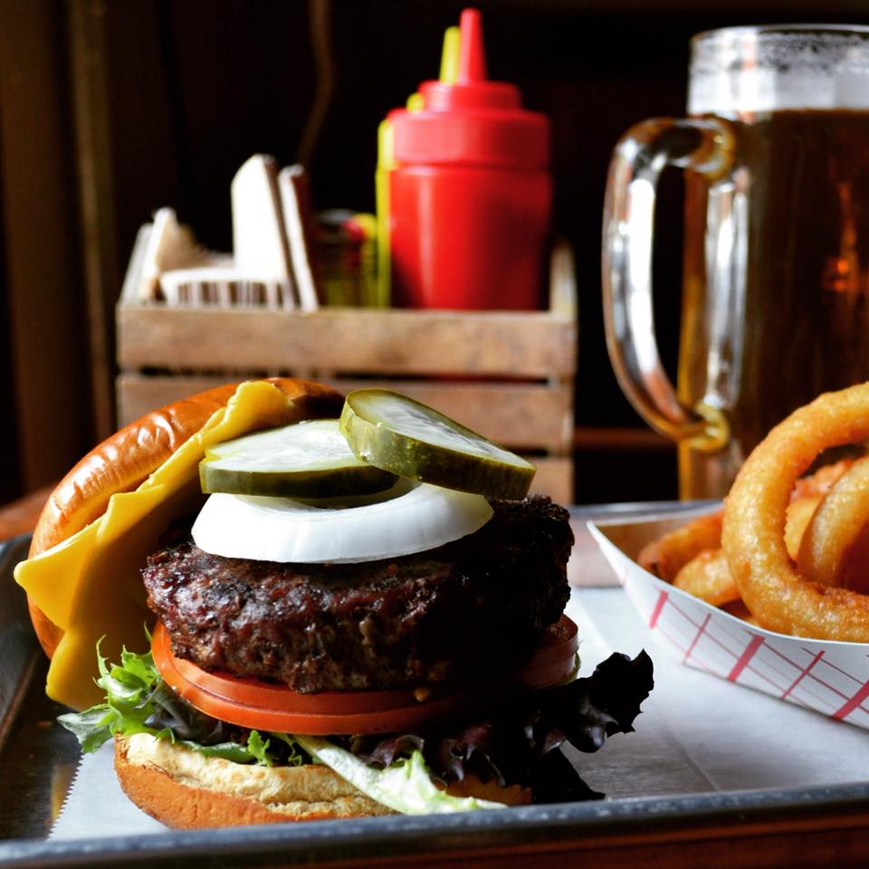 Cheese burger with lettuce, tomato, onion and pickles on a tray with onion rings on the side and a beer and ketchup container in the background