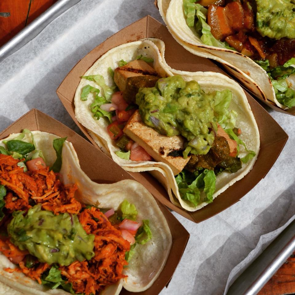 Assorted tacos with lettuce, tomato and guacamole