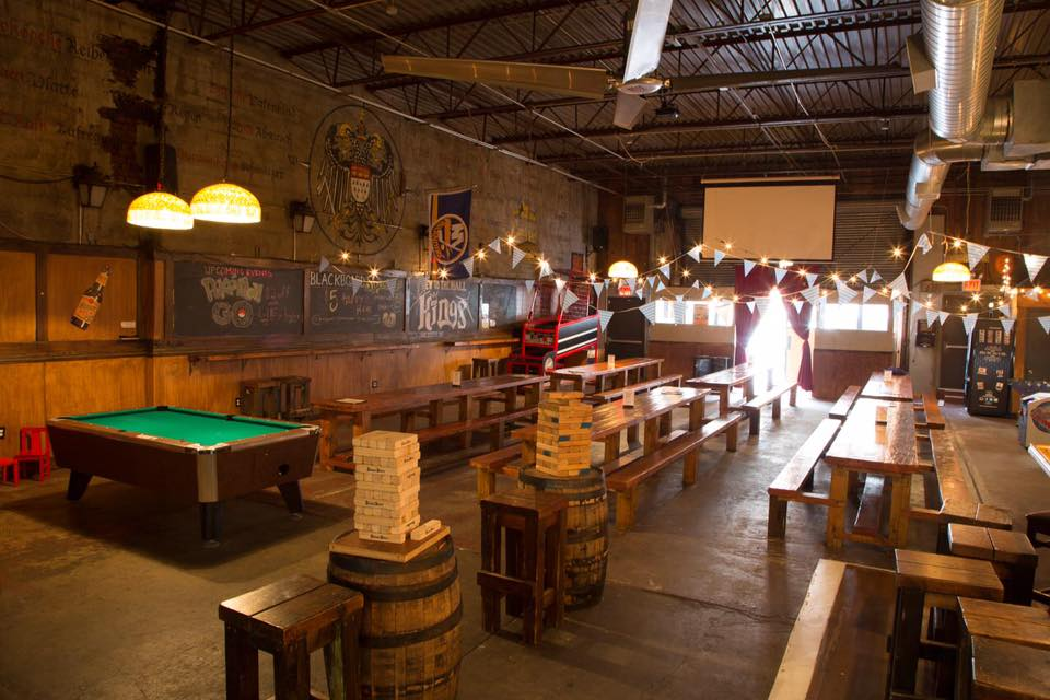 Interior bar area with a pool table, wooden chairs and tables and assorted tables games