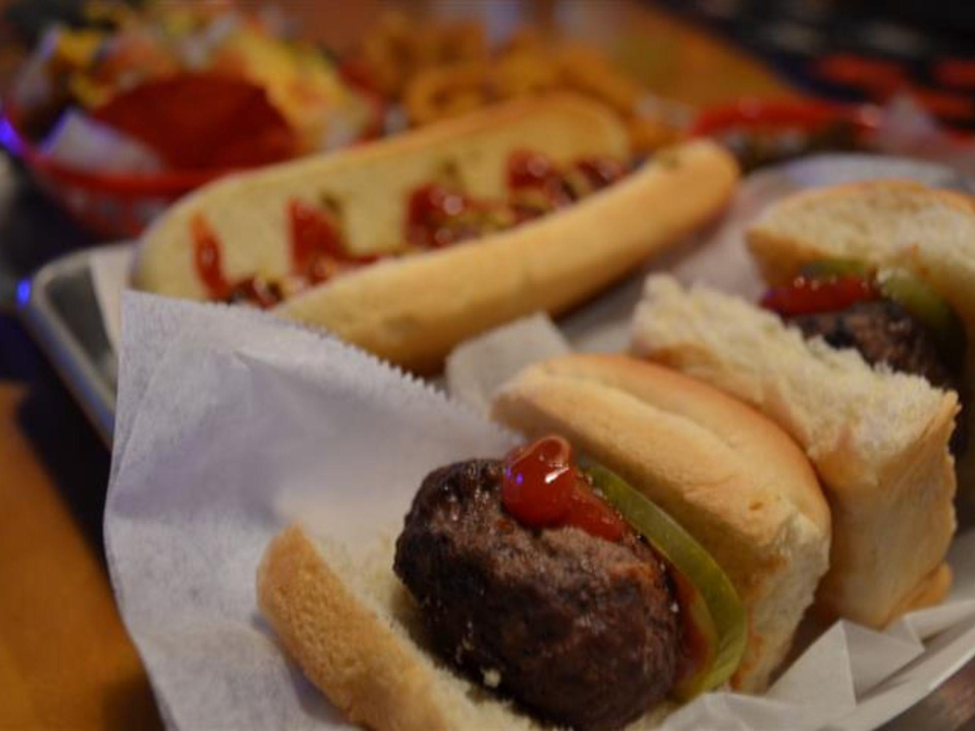 Close up of sliders with a hot dog and fries blurred in the background