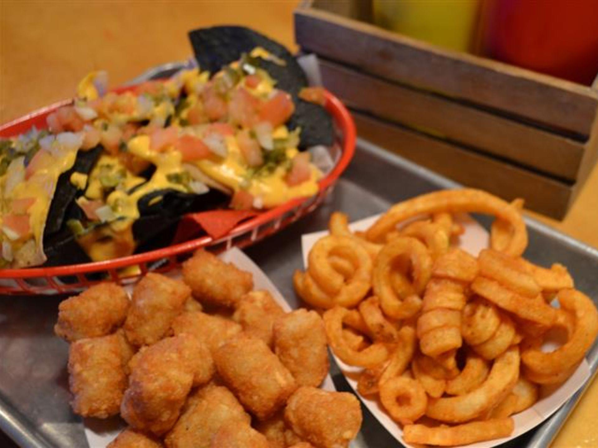 Basket of nachos, tater tots and curly fries