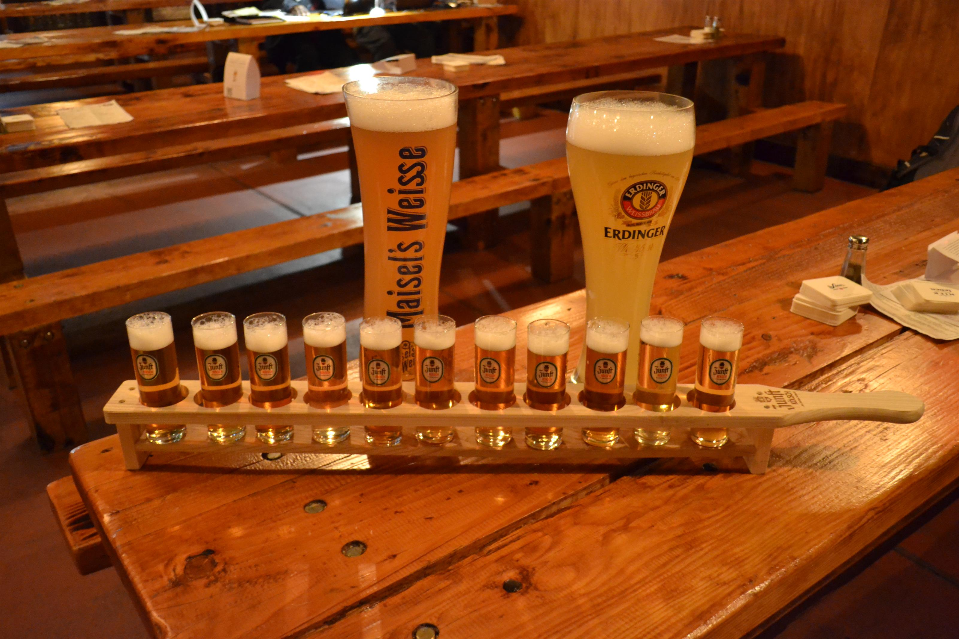 A flight of light beers with two large beer steins filled with beer on a wooden table-top