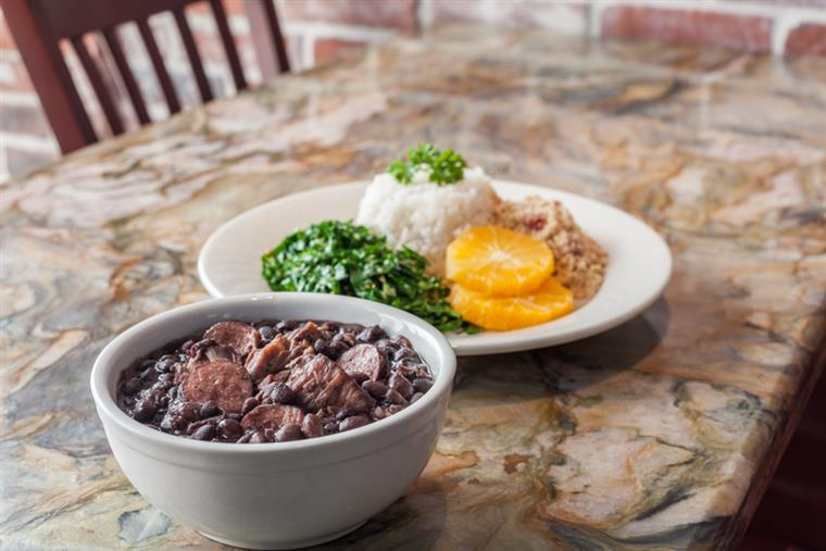 Picanha and black beans in bowl with sides of rice, collard greens, orange slices on marble table.
